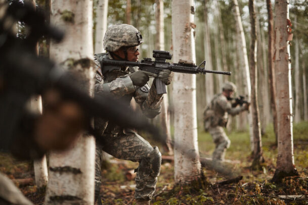 american soldiers training in forest with rifles