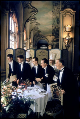 waiters in a luxury restaurant looking outside a window