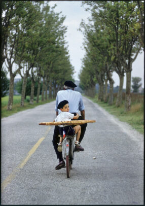 boy on a bicycle with his granfather holding a baguette