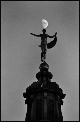 statue and the moon on background