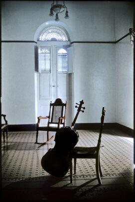 a cello leans agains a chair