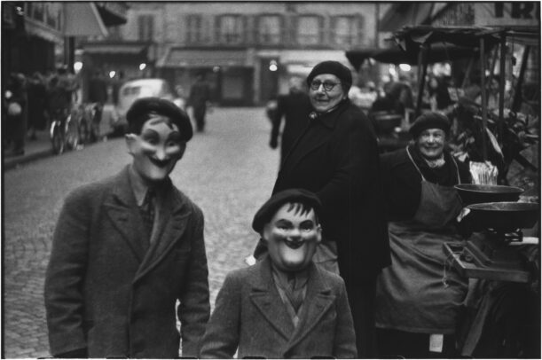 two children with a mask and a woman watching them