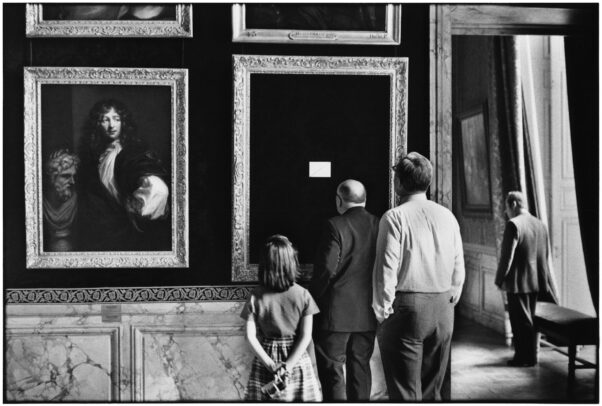 three people watching an empty frame in Versailles