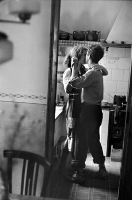 Photographer Robert Frank dancing in the kitchen with his wife