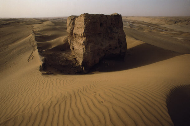 The shell of a Han Wall beacon tower stands in relief against the sand dunes