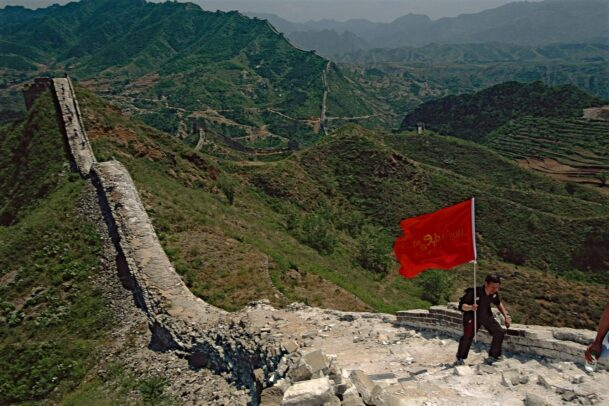 man with a red flag at the Simitai wall