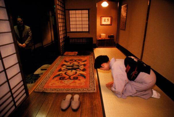 a woman bows to greet guests at a japanese inn