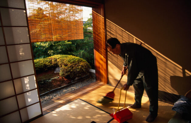 man cleaning a room in a japanese inn with garden outside