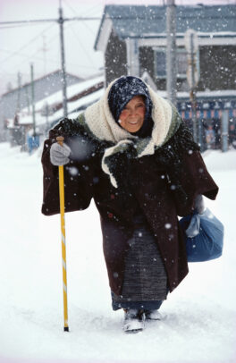 old woman walking on a snowy street with a cane