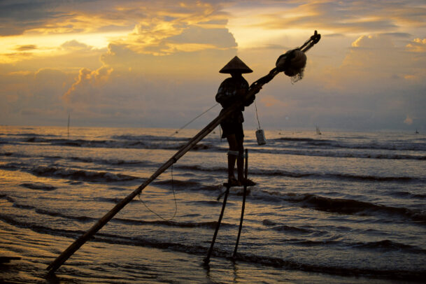 fisherman on stilts in the sea