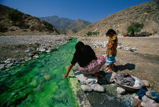 woman and her daughter near a creek in a desert area