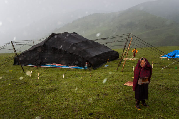Members of a nomad family weather a sudden storm outside their yak-wool tent