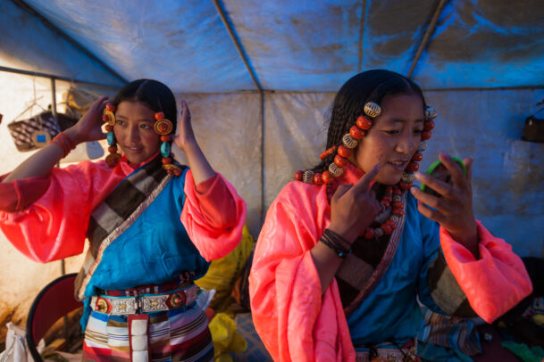 Tibetan girls decked in festival finery, turquoise, coral, and silver.