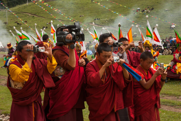 Shechen monks record an event with cameras and videocameras