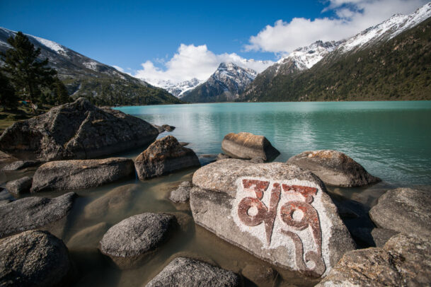 A mani prayer stone sits on the shore of Lhamo Latso lake