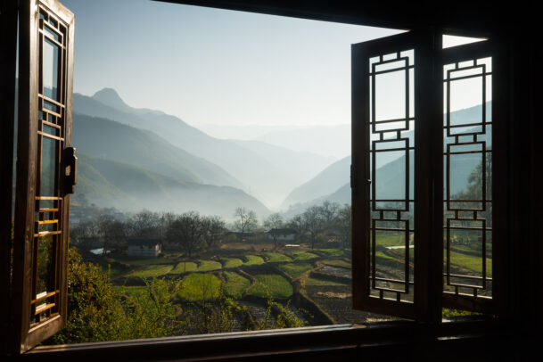 view of the terrace rice fields and misted peaks through a tibetan window