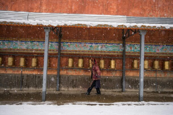 A villager walks past bronze prayer wheels lining a wall while snowing