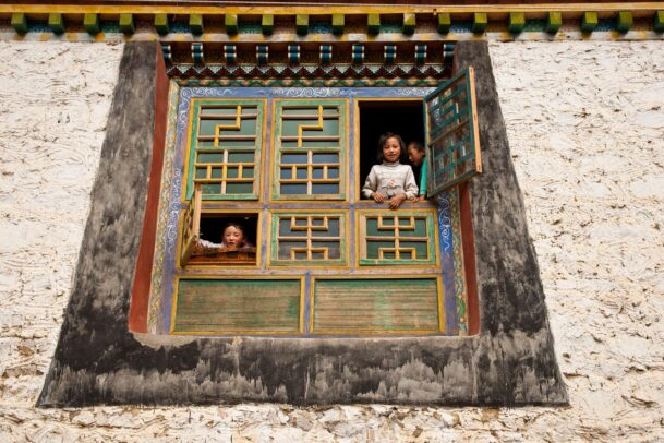 Children from intricately decorated windows, framed by traditional Tibetan architecture