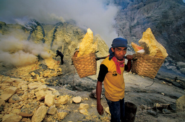 miner with baskets on his shoulder full of sulfur