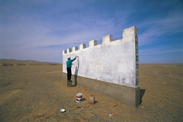 a man starts work on a Great Wall billboard in the desert near Dunhuang