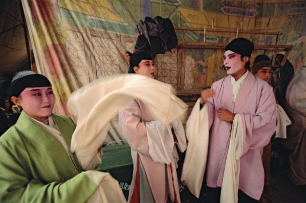 chinese singers in an opera troupe wait to perform