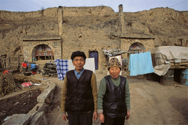 chinese man and women in front of their house
