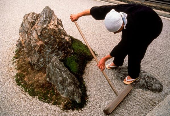 man working on gravel in a Japanese garden
