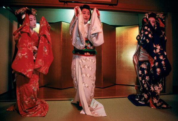 Three geisha in exquisite kimono dance at a party
