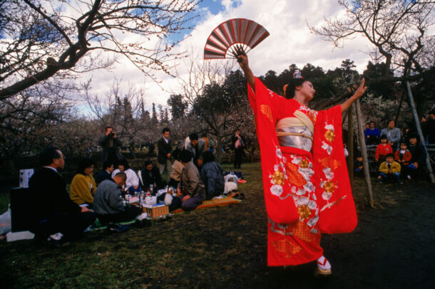 japanese woman in kimono holding a fan dancing in a park with people having a picnic