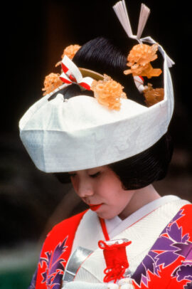 a japanese bride wearing the elaborate kimono and headpiece for the Shinto ceremony