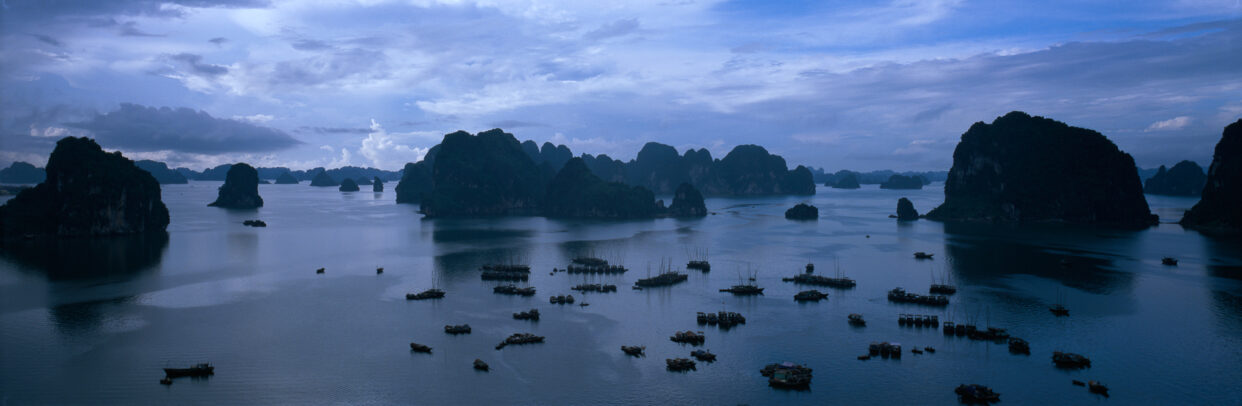 Groups of fishing boats dot the placid waters of Halong Bay