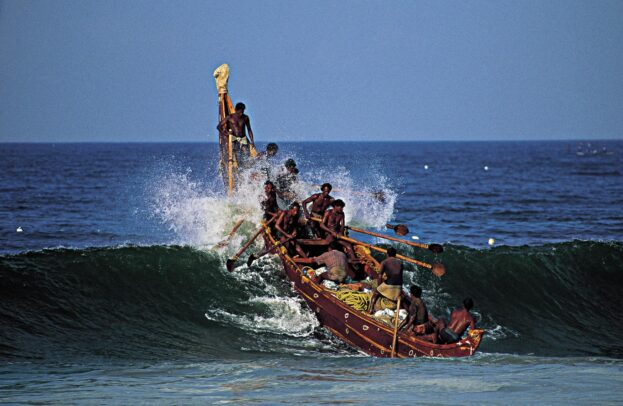 Traditional Indian fishing boat on a wave
