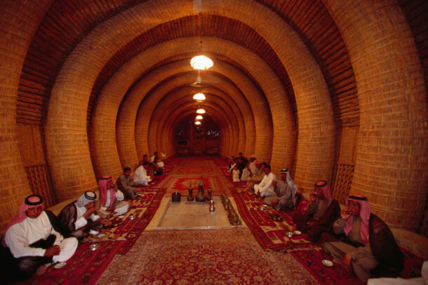 men sitting in a traditional communal house built from lake reeds north of Basra