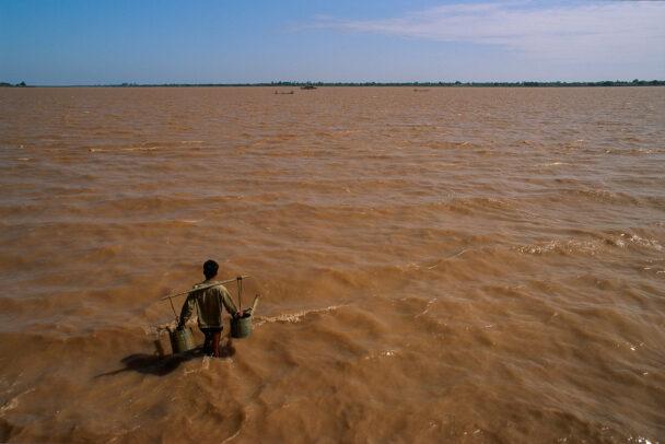 A man walks in the flood-swollen Mekong to fill his irrigation buckets