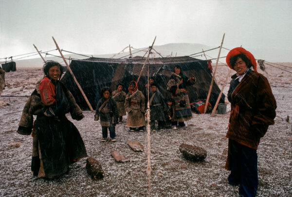 A Tibetan family in front of their yak-skin tent house while raining