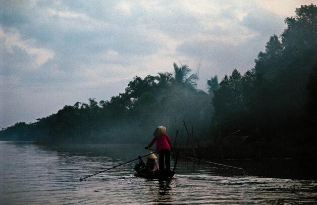 In the dawn haze, two women go to market in Camau, southern Vietnam.