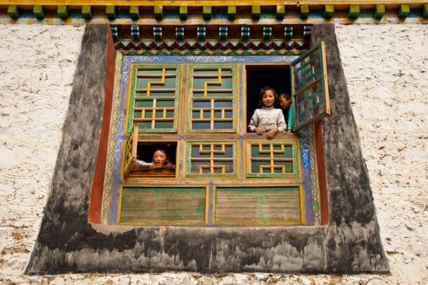 Children peer from intricately decorated windows, framed by traditional Tibetan architecture