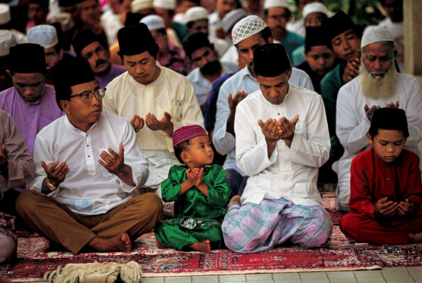 men and a child praying in a mosque