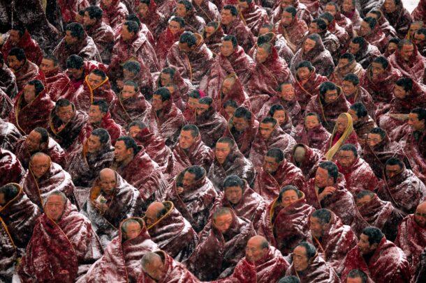 in a blizzard monks await the start of morning prayers in Labrang Monastery, Tibet.