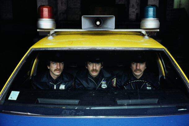 three policemen in a yellow car of police