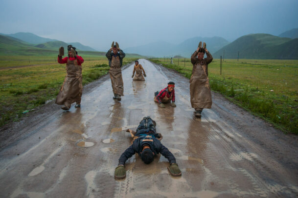 buddhist pilgrims prostate themselves on their way to Lhasa