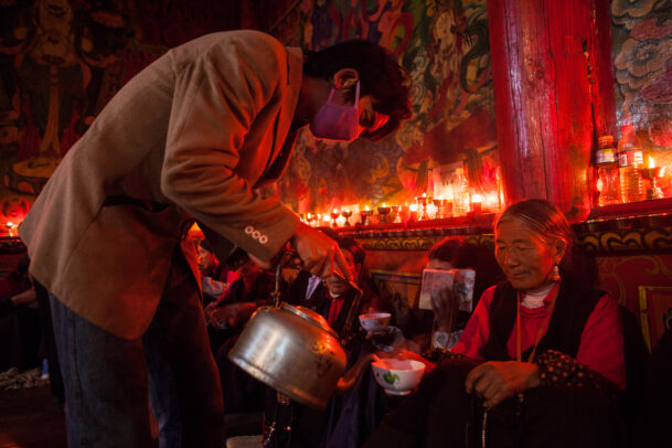 man pouring tea to an old lady in a tibetan monastery