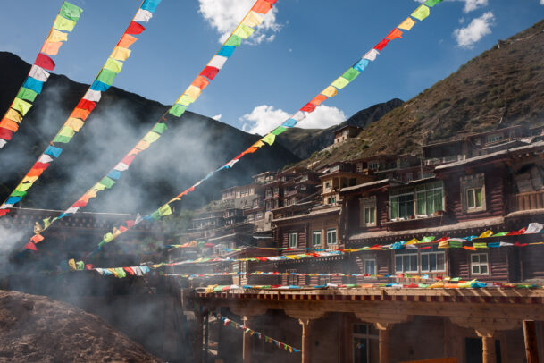 prayer colored flags near a building on a hill