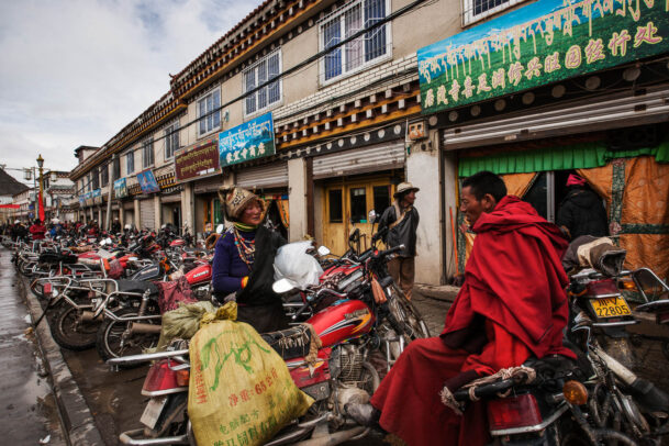 monks and a woman chatting near a long row of motorcycles