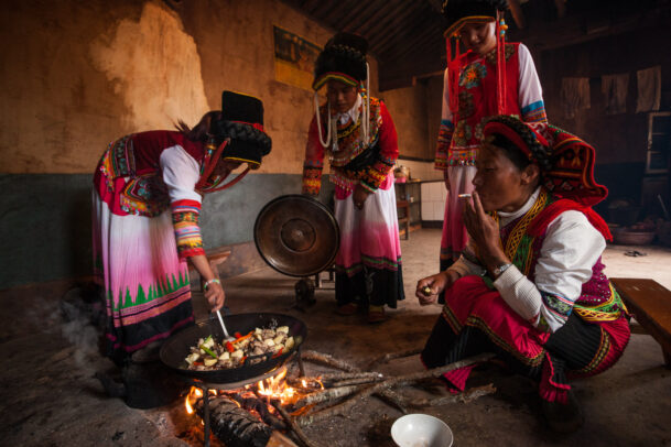 Yi wome prepare a meal at the fireplace in their village