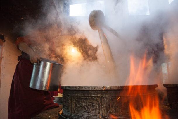 monk preparing yak butter tea with a big cauldron