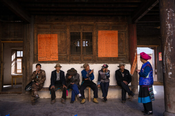 chinese men sitting on a bench chatting