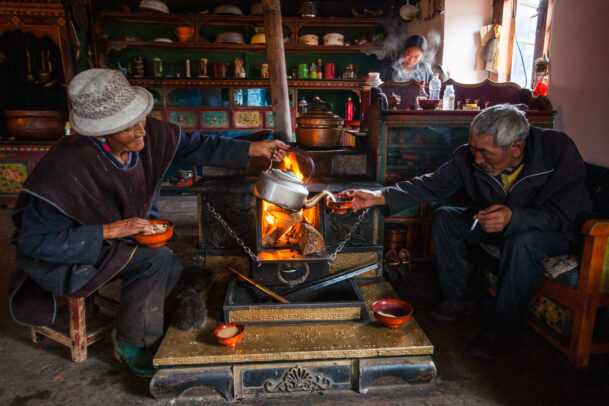 an old woman pouring yak butter tea to an old man in a bar in Tibet