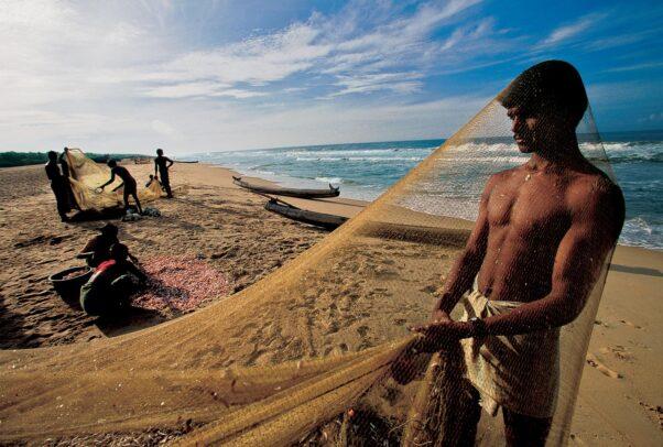 fishermen clean their nets on Somatheeram Beach