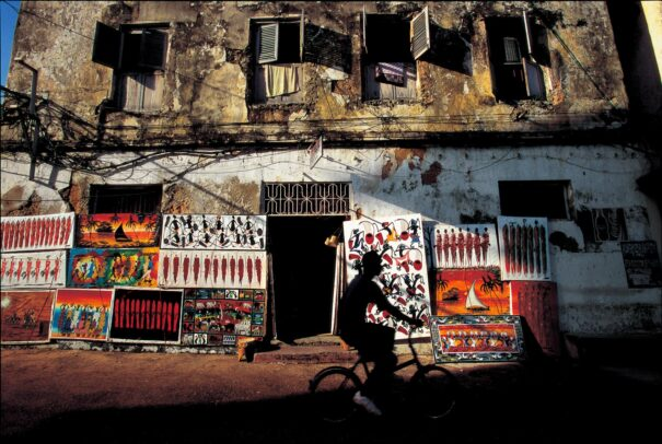 crumbling building in Zanzibar with paintings leaning against his walls